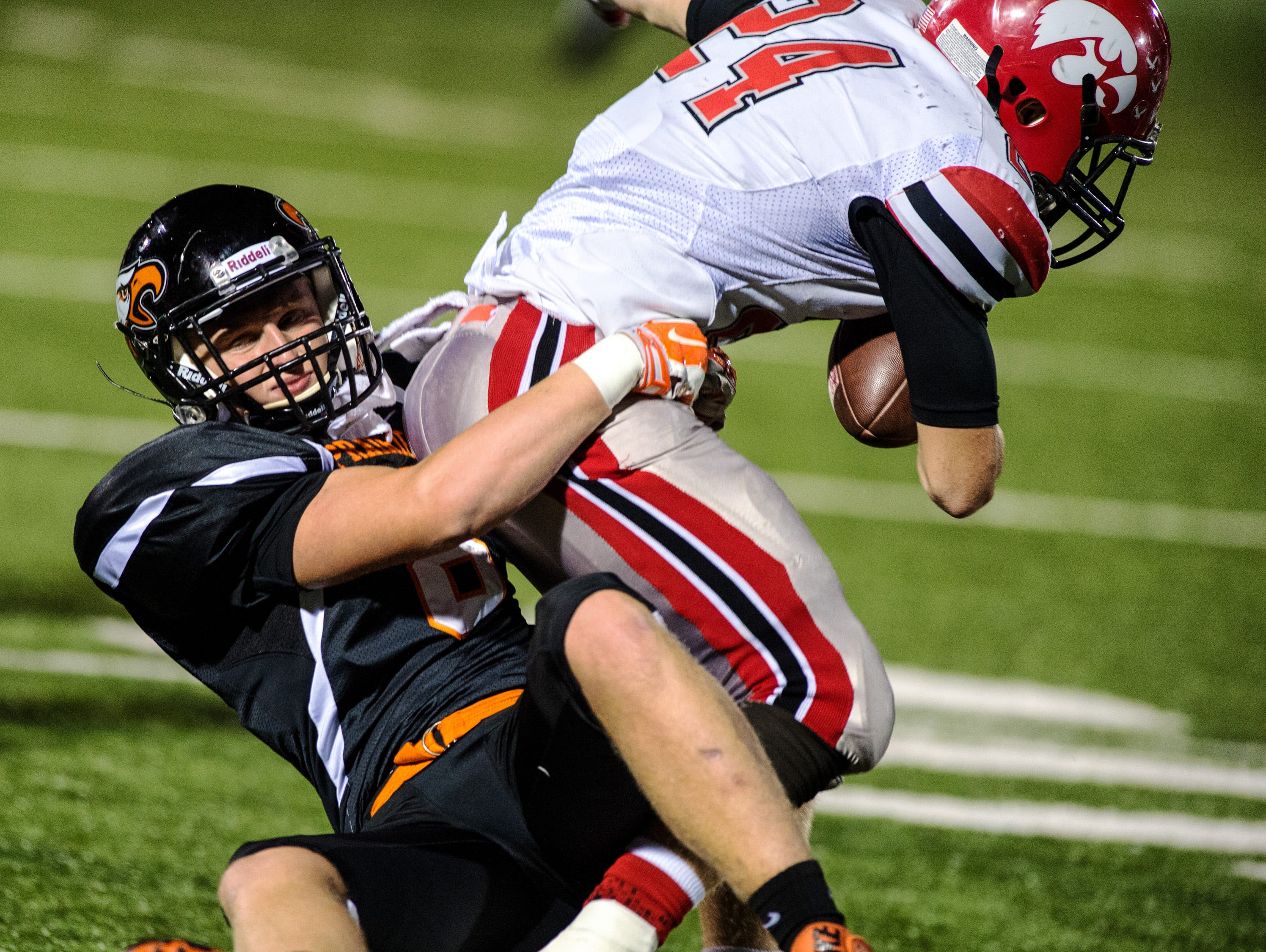 Iowa City High's Bryce Frantz (24) gets tackled by Cedar Rapids Prairie's Zachary Ganske (24) during the first half of play on Friday, October 2, 2015 in Cedar Rapids. (Justin Torner/Freelance for the Press-Citizen)