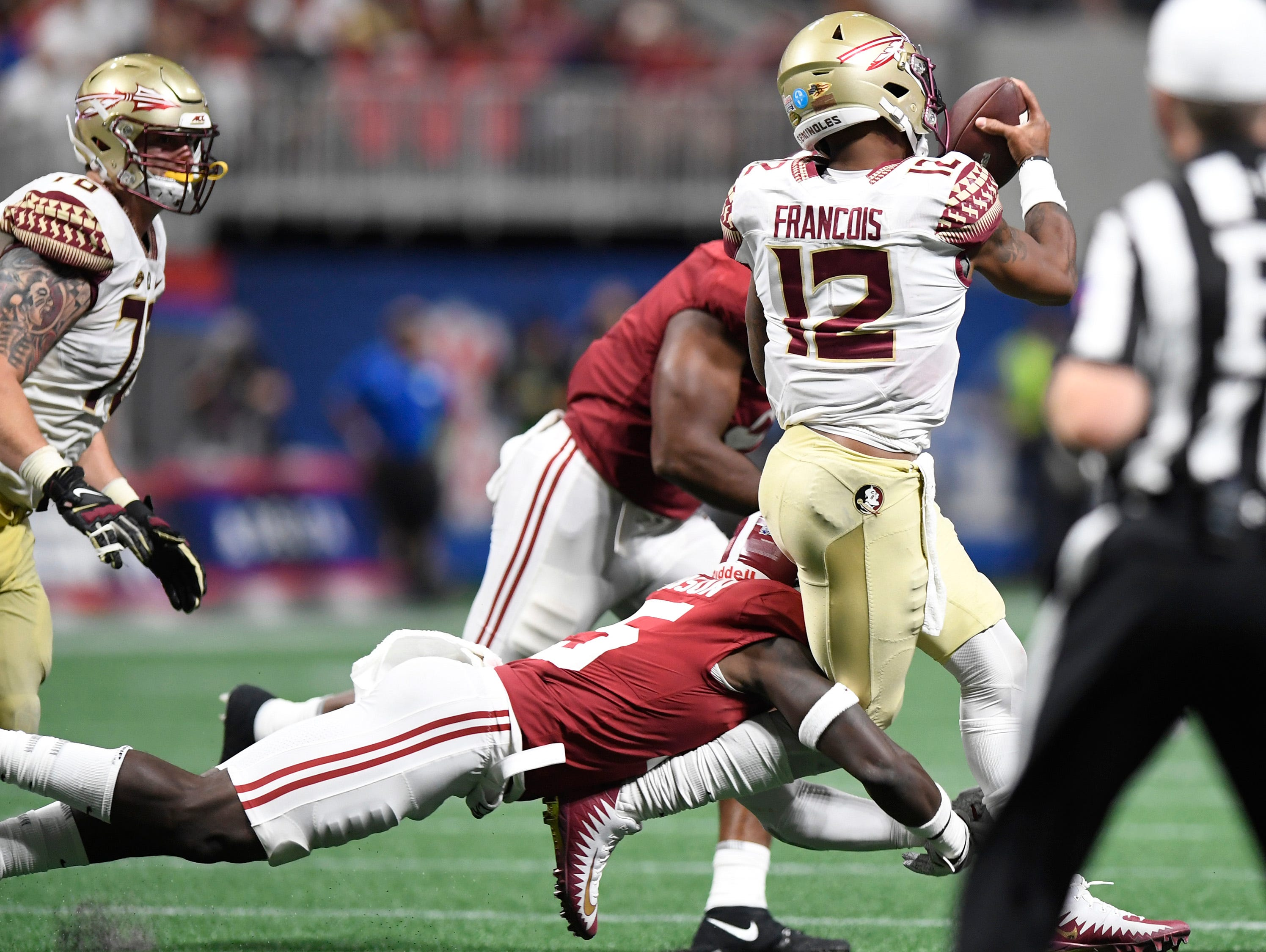 Alabama defensive back Ronnie Harrison (15) tackles Florida State quarterback Deondre Francois (12) injuring him in the Chick-fil-a Classic at the Mercedes - Benz Stadium in Atlanta, Ga., on Saturday September 2, 2017.