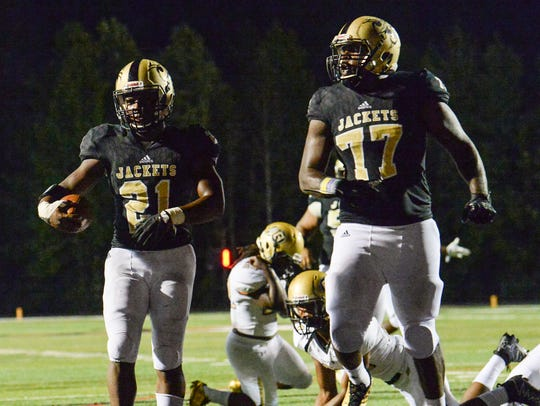 T.L. Hanna lineman Kavesz Shepard (77), right, watches