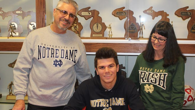 Roeper senior Simon Roennecke signs his intent letter to Notre Dame under the watchful eyes of his parents Werner and Patricia on Wednesday afternoon.