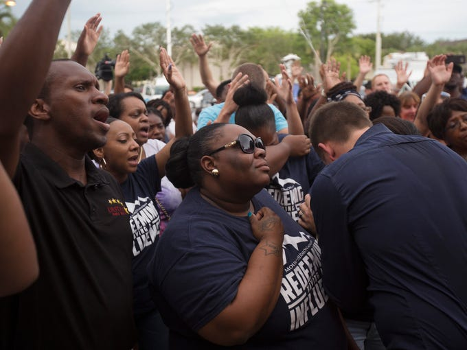 Shaniqua Young,center, takes part in prayer service