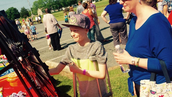 Cameron Kaelin and his mom, Julie, enjoy the festivities Saturday during a picnic put together by Salisbury Christian School's Interact Club to raise money for Cameron who was diagnosed with cancer.