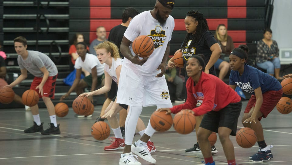 Former NBA player, Reggie Evans, center, teaches middle