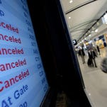 A departure screen shows cancellations at Detroit's airport on Oct. 29, 2012.