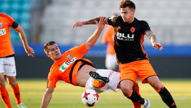 FC Lausanne-Sport's Andrea Maccoppi, left, fights for the ball with Valencia FC's Santi Mina during a friendly soccer match at the Stade Olympique de la Pontaise, in Lausanne, Switzerland.