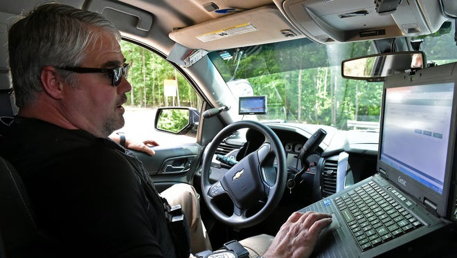 Rankin County Interdiction Unit Detective Chris Picou watches cars pass by Monday on the eastbound lane of Interstate 20. Money, drugs and other property are forfeited during drug interdictions.