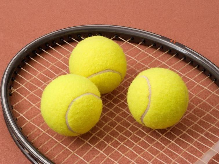 Three tennis balls on a racket head