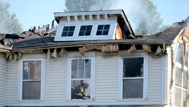 A Nashville firefighter works a house fire from inside a home in Madison on Monday, May 23, 2016.