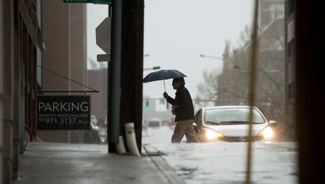 Downtown pedestrians deal with rain on Wednesday, March 1, 2017.