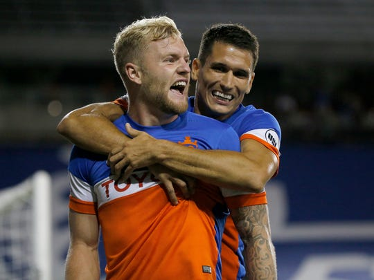 FC Cincinnati's Danni Konig (11) hugs defender Sem de Wit (51) as he celebrates after scoring his team's third goal of the game in the second half of the USL soccer match between FC Cincinnati and the Ottawa Fury at Nippert Stadium in Cincinnati on Wednesday, Aug. 23, 2017. FC Cincinnati secured a 3-1 win over Ottawa before more than 20,000 fans.