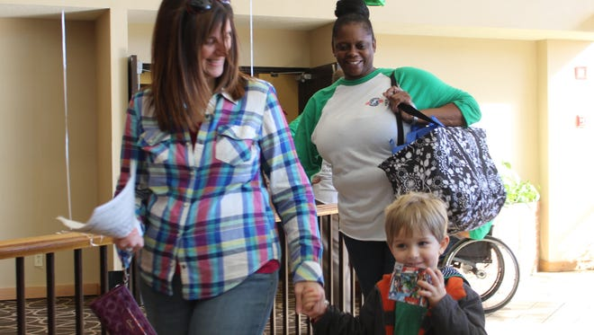 A volunteer at December's Operation Homefront event at the Quality Inn, helps one family carry their holiday meal to their car. The group is hosting a baby shower for moms-to-be this weekend.