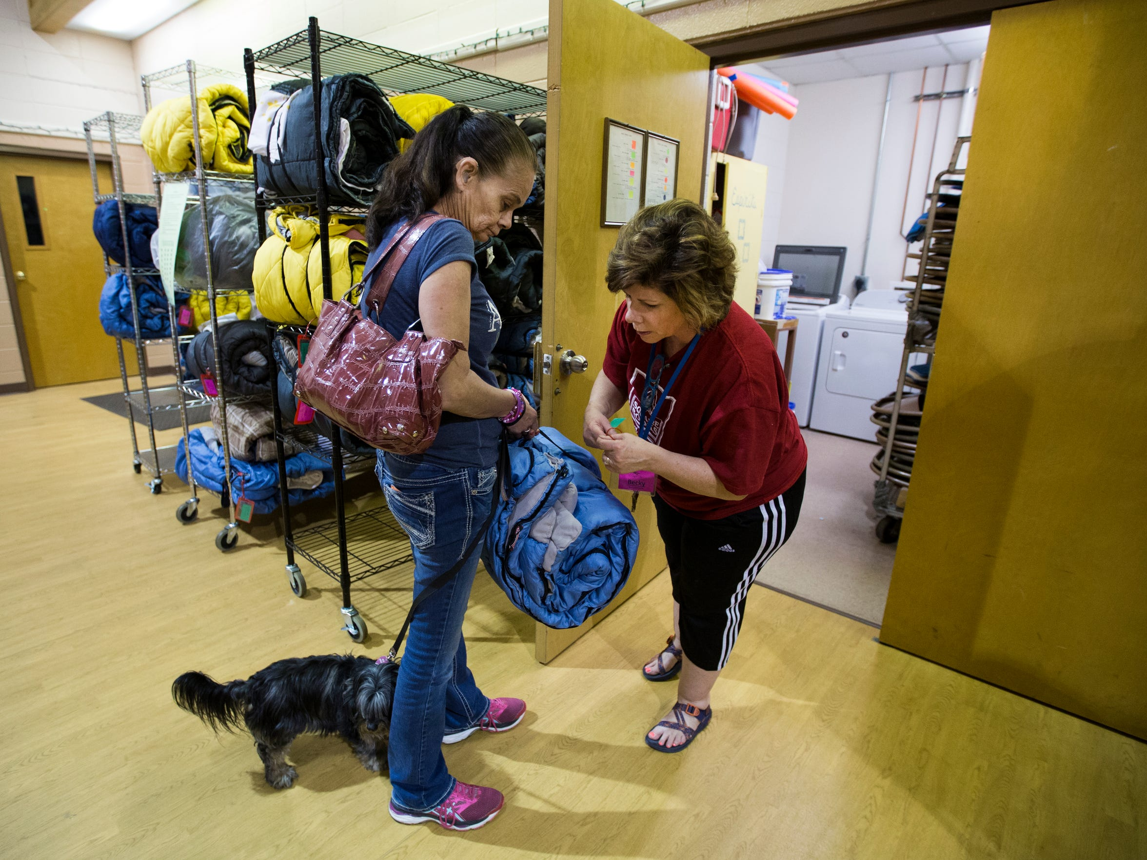 Safe to Sleep volunteer Becky Solari retrieves a sleeping bag for Julie Starbuck, 51, on Tuesday, April 24, 2018.