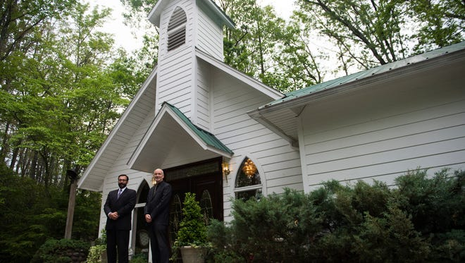 From left co-owners of Chapel in the Park Guy Jacobs and Lee Bennett stand in front of the chapel in Gatlinburg on Friday May 19, 2017. Bennett and Jacobs say business is down 40% compared to this time last year due to the November wildfires.