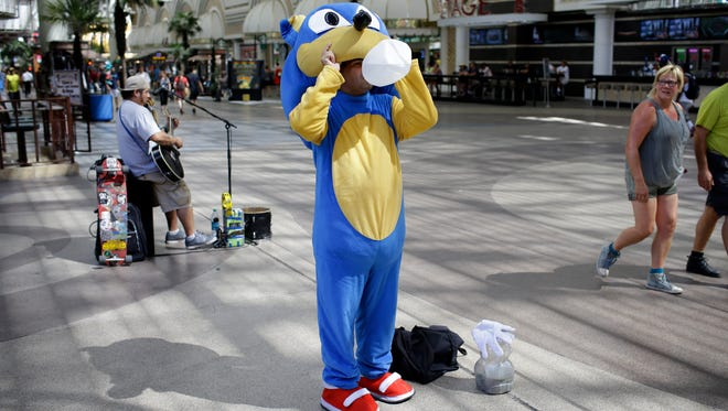 Street performer Daniel Gallegos drinks water while the temperature remain in the triple digits in Las Vegas on July 24, 2014.