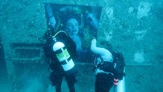 """Divers hang a large photo illustration on the superstructure of the 523-foot-long Gen. Hoyt S. Vandenberg that was intentionally sunk almost 10 years ago off Key West, Fla., in the Florida Keys National Marine Sanctuary. The artwork is one of 24 created by Austrian photographic artist Andreas Franke as part of his """"Plastic Ocean Project"""" designed to communicate the need to protect the world's oceans from plastic refuse."""