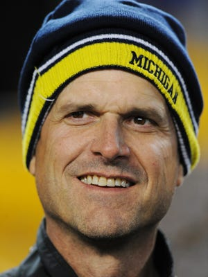 Former San Francisco 49ers head coach and new Michigan football coach, Jim Harbaugh is on the sideline to watch his brother Baltimore Ravens head coach John Harbaugh, before an NFL wildcard playoff football game against the Baltimore Ravens, Saturday, Jan. 3, 2015, in Pittsburgh. (AP Photo/Don Wright)