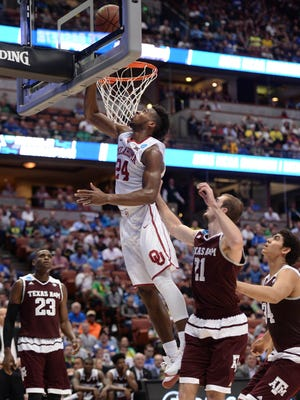 Oklahoma Soonersguard Buddy Hield (24) moves to the basket against Texas A&M Aggies guard Alex Caruso (21) during the first half  of the semifinal game in the West regional of the NCAA tournament at Honda Center.