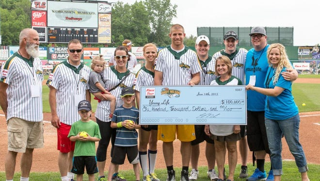 Green Bay Packers receiver Jordy Nelson and his wife Emily, middle, present a $100,000 check to Young Life Green Bay before the start of the second annual Jordy Nelson Charity Softball Game at Fox Cities Stadium in Grand Chute on Sunday. Young Life area director Kirk Foote and his wife Amy, pictured on right, accept the check.