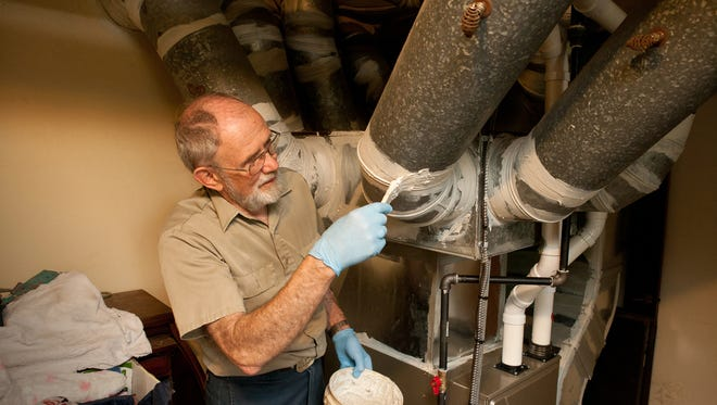 David Legg of People Working Cooperatively weatherizes a furnace as part of PWC's free home weatherization program in 2013.