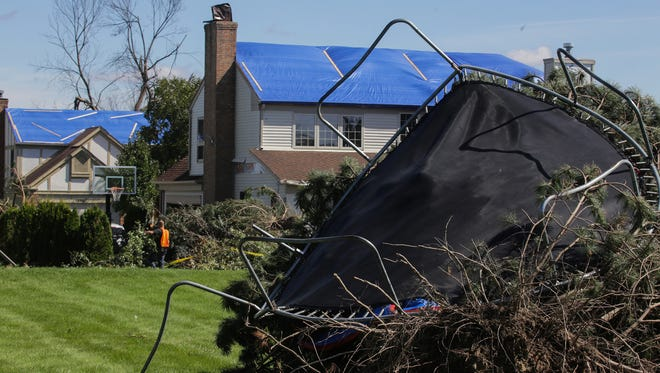 A trampoline wraps around an uprooted tree as houses show roof damage on Grandview Dr. in Rochester Hills today after a category EF1 tornado hit the area on Sunday.