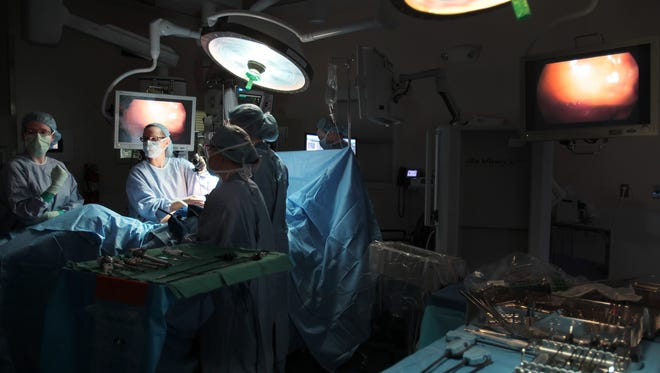 IU Health surgeon Emma Rossi (center) places probes into a patient during a new procedure for uterine cancer surgery at IU Health Simon Cancer Center on April 1, 2014.