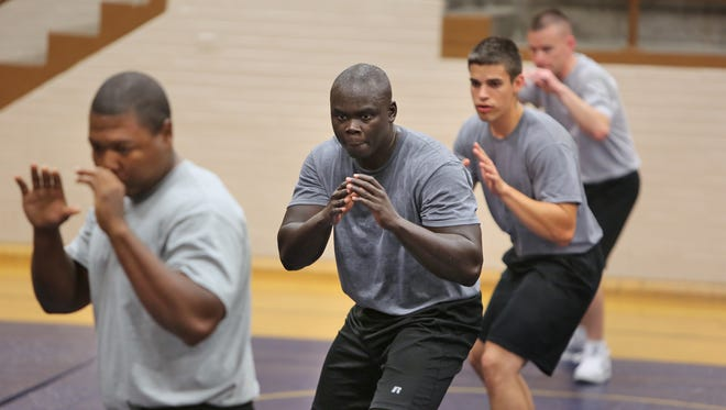 Indianapolis Metropolitan Police Department recruits take the fighting stance as they warm up June 19, 2014, for survival training at the police academy.