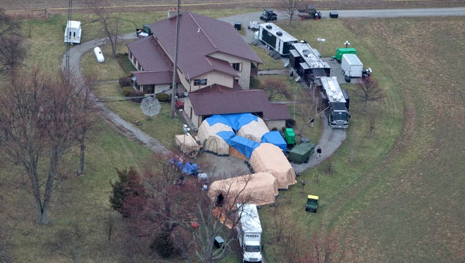 FBI agents on April 2, 2014, work around a home in Rush County, Ind., to confiscate thousands of artifacts from Native Americans, Russia, China, and other nations from a private collection.