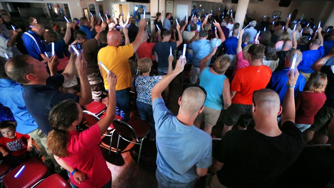 Fellow officers, friends and the community came together as one while holding up glow sticks during a blue light prayer vigil held at the FOP Lodge #86 in honor of fallen IMPD officer Perry Renn on Wednesday, July 9, 2014.