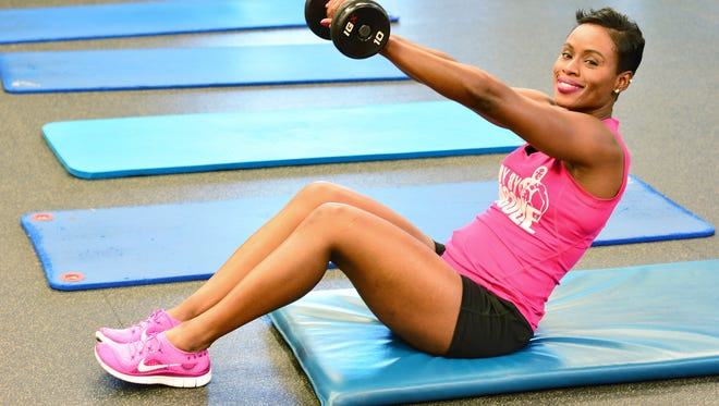Nicole Randolph demonstrates an ab excercise with a dumbbell.