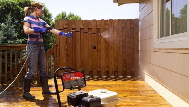 A woman cleans off overspray by rinsing the siding and windows with clean water at a low pressure to remove chemical residue.  (AP Photo/Copyright The Family Handyman)