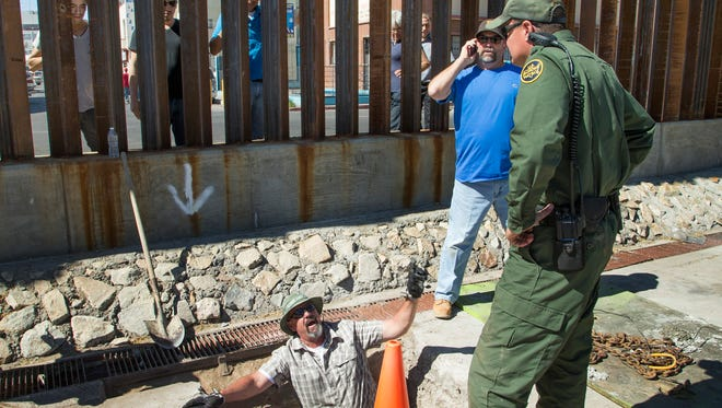 U.S. Customs and Border Protection and contract workers seal a drug tunnel with concrete in Nogales, Ariz., on Thursday while bystanders peer through the border fence from the Mexican side.