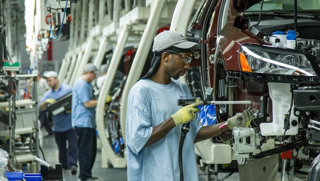 In this June 12, 2013, file photo, workers assemble Volkswagen Passat sedans at the German automaker's plant in Chattanooga, Tenn.