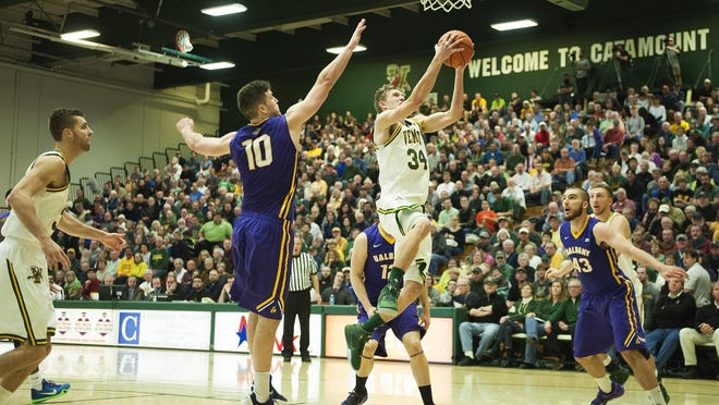 Catamounts guard Kurt Steidl (34) leaps past Albany's Mike Rowley (10) for a layup during the men's basketball game between the Albany Great Danes and the Vermont Catamounts at Patrick Gym on Saturday afternoon.