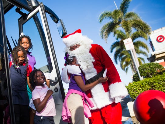 """Fredlisha Johnson hugs Santa Claus as she exits the bus for the """"Shop With a Sheriff"""" event at Target in North Naples on Thursday, Dec. 14, 2017. The Collier County Sheriff's Office and the Jewish Federation of Greater Naples partnered for third year in a row to help 65 children and their families during the holiday season."""