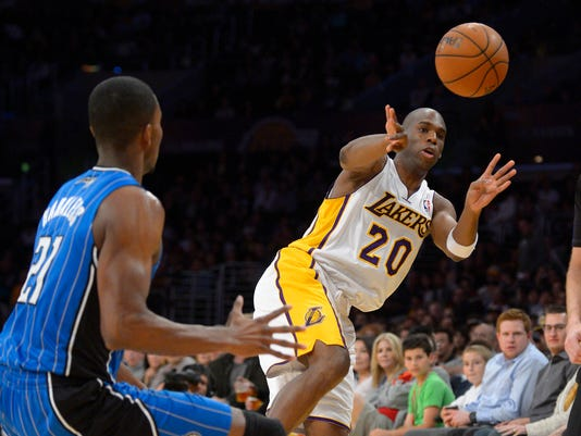 Los Angeles Lakers guard Jodie Meeks, left, passes the ball as Orlando Magic forward Maurice Harkless defends during the first half of an NBA basketball game, Sunday, March 23, 2014, in Los Angeles.  (AP Photo/Mark J. Terrill)