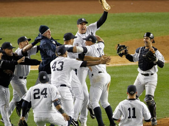 In this Nov. 4, 2009, file photo, New York Yankees' Mark Teixeira, center, and teammates celebrate after defeating the Philadelphia Phillies, 7-3, in Game 6 of the World Series, in New York.