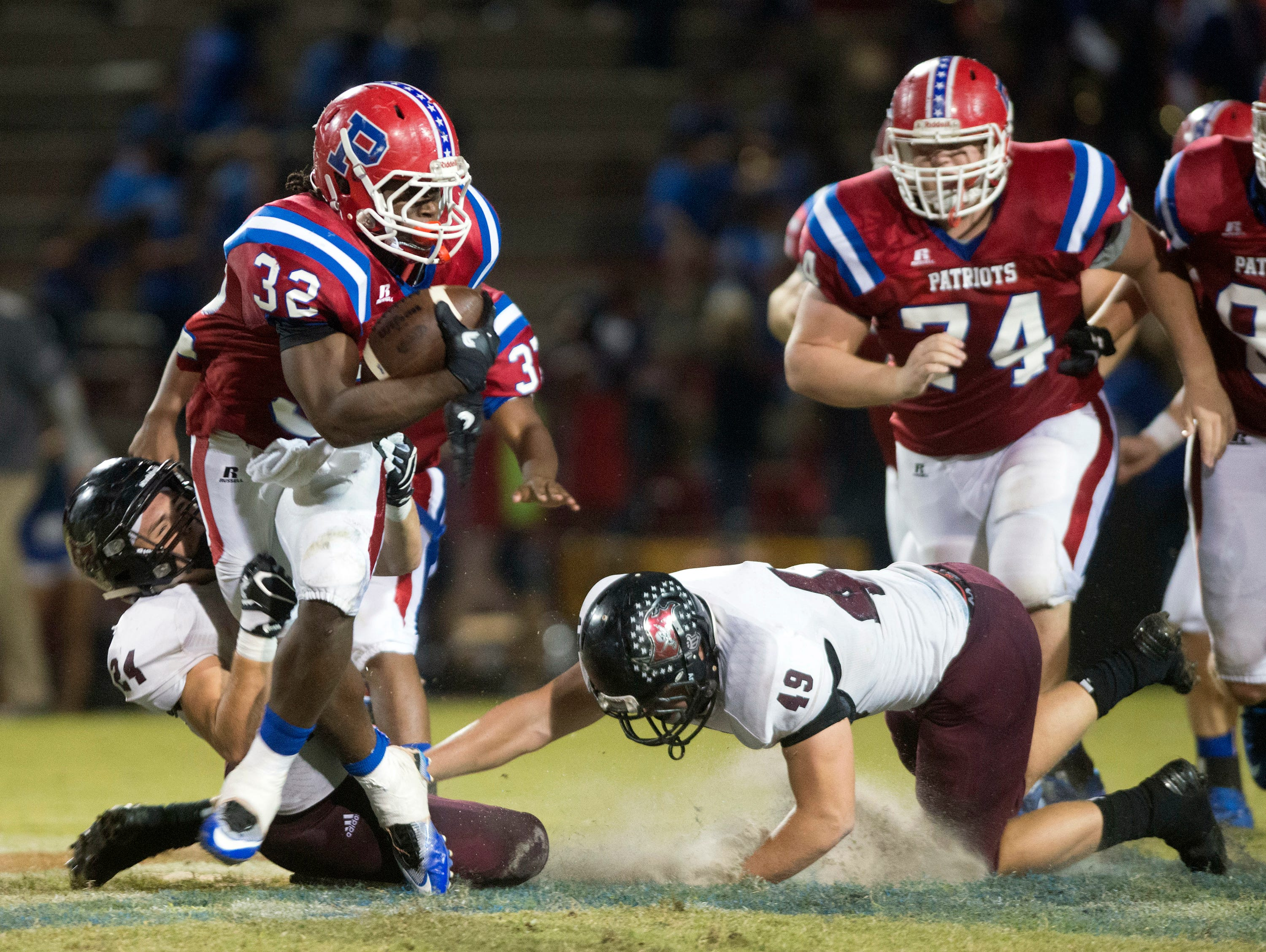 Pace High School running back Anthony Johnson, Jr. (No. 32) gives Navarre High School corner, Reese Parker, (No 24) and end, Ryan Struck, (No. 49), the slip to gain extra yards during Friday night's District 2-6A matchup.
