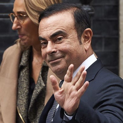 Nissan CEO Carlos Ghosn waves as he leaves No. 10 Downing