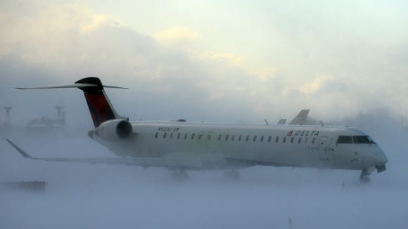 A Delta Connection flight at Buffalo's airport makes its way through a snowstorm on Nov. 18, 2014.