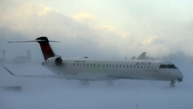 Lake-effect snow storm with freezing temperatures affected travel, like this plane that negotiated its way through the snow at Buffalo Greater International Airport, in Buffalo, N.Y. Tuesday, Nov. 18, 2014. Temperatures fell to freezing or below at recording stations in all 50 states on Tuesday morning, from the highest elevations in the mountains of Hawaii to the snow-paralyzed Buffalo area in New York. (AP Photo/Gary Wiepert) ORG XMIT: NYGW101