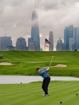 The New York City skyline looms in the background, as Peter Barzilai tees off on hole No. 4.