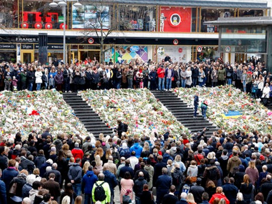 People observe a minute of silence in Stockholm, Sweden, Monday, April 10, 2017, to honor the four killed victims and 15 injured in a fatal truck attack. The attack was allegedly carried out by an asylum-seeker from Uzbekistan who drove the stolen vehicle into a crowd of shoppers on a busy Friday afternoon in downtown Stockholm.