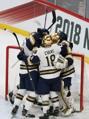 Notre Dame's Jake Evans (18) celebrates with teammates