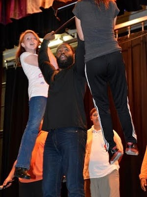 """Willie Green, a South Jersey Youth Alliance motivational speaker and a former NFL running back, """"lifts"""" students during Veterans Memorial School's Family Fun Night on Oct. 22."""