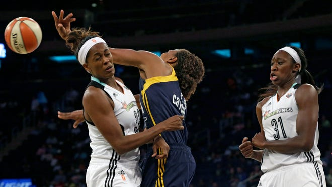 Indiana Fever forward Tamika Catchings, center, passes the ball past New York Liberty forward Swin Cash, left, and center Tina Charles during the first half of Game 1 of the WNBA basketball Eastern Conference finals, Wednesday, Sept. 23, 2015 at Madison Square Garden in New York.