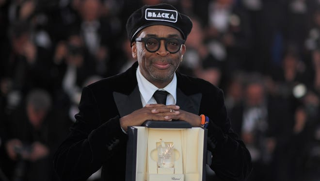 """Spike Lee poses with his trophy on May 19, 2018 during a photocall after he won the Grand Prix for the film """"BlacKkKlansman"""" at the Cannes Film Festival."""