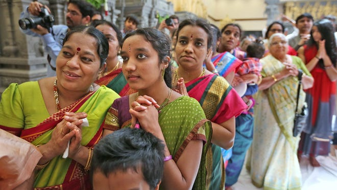 Devotees look on during the Moorthi Abhishekam ritual of bathing the deities Sunday, June 7, 2015, the last day of the five-day celebration at the Hindu Temple of Central Indiana. The celebration unveiled the $10 million expansion of the temple, which added a worship hall that includes 17 shrines. The ceremonies consecrated the new space and blessed the stone sculpture deities installed in the temple.