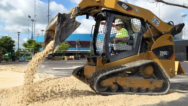Ronnie McWhorter uses a front loader to spread some of the 500 tons of sand needed to create two additional courts for the AVP/FIVB Cincinnati Open Beach Volleyball Tournament at the Lindner Tennis Center in Mason.