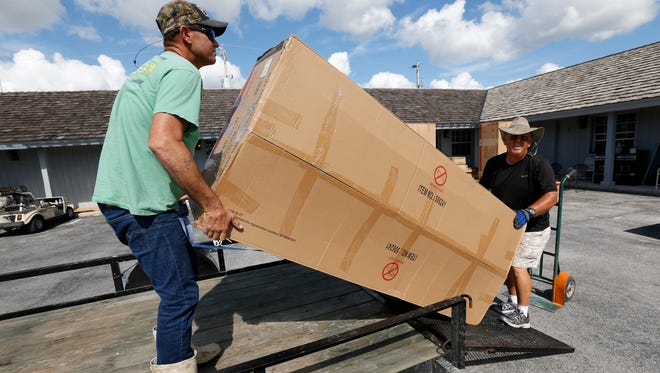 In this Thursday, Nov. 9, 2017 photo, volunteer Danny Floyd, right, of Weatherford, Okla,, helps Kenny and Brittany Smallwood, left, load new furniture donated by the nation's Churches of Christ, at Outdoor Resorts of Chokoloskee, in Chokoloskee, Fla. Kenny and Brittany Smallwood say FEMA rejected their assistance request after an 8-minute inspection even though Hurricane Irma's torrential rains poured through the hole it tore in their home's roof, destroying much of their furniture and causing extensive damage. They say they were denied financial aid because one room remains livable. They share it with their three young sons.