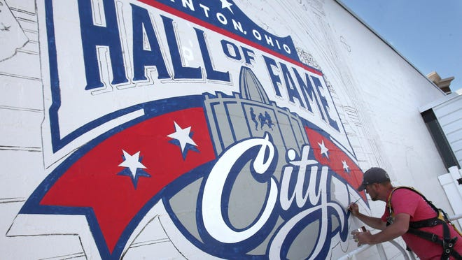 Artist Dirk Rozich paints a football mural on the side of a building near Cleveland Avenue and Sixth Street NW in downtown Canton.